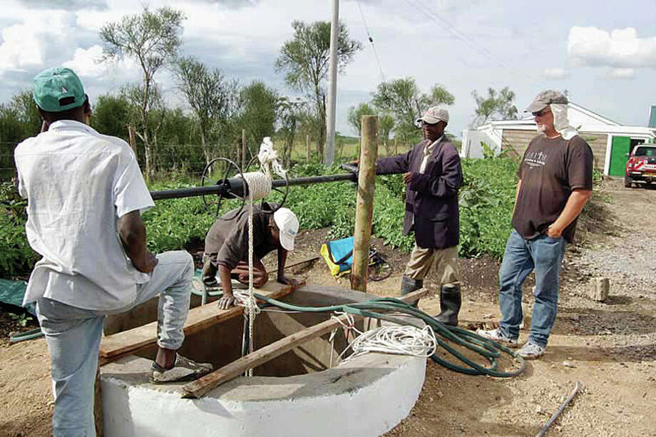 Chuck McDonald works on the well with a couple of workers. Chuck and Tammy McDonald live full-time in Kenya, where they are doing mission work.