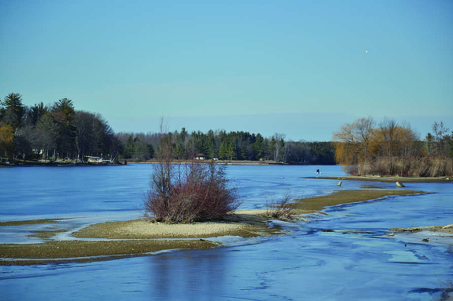 """Normally, just a tuft of island is visible here on Wixom Lake along Dundas Road. With the lake level about three feet down — as is usual in winter, according to the company that operates the dam forming the impoundment — far more of the lake bottom is """"high and dry."""" In the background is an ice fisherman trying his luck on this year's thin ice. Photo: Steve Griffin   For The Daily News"""
