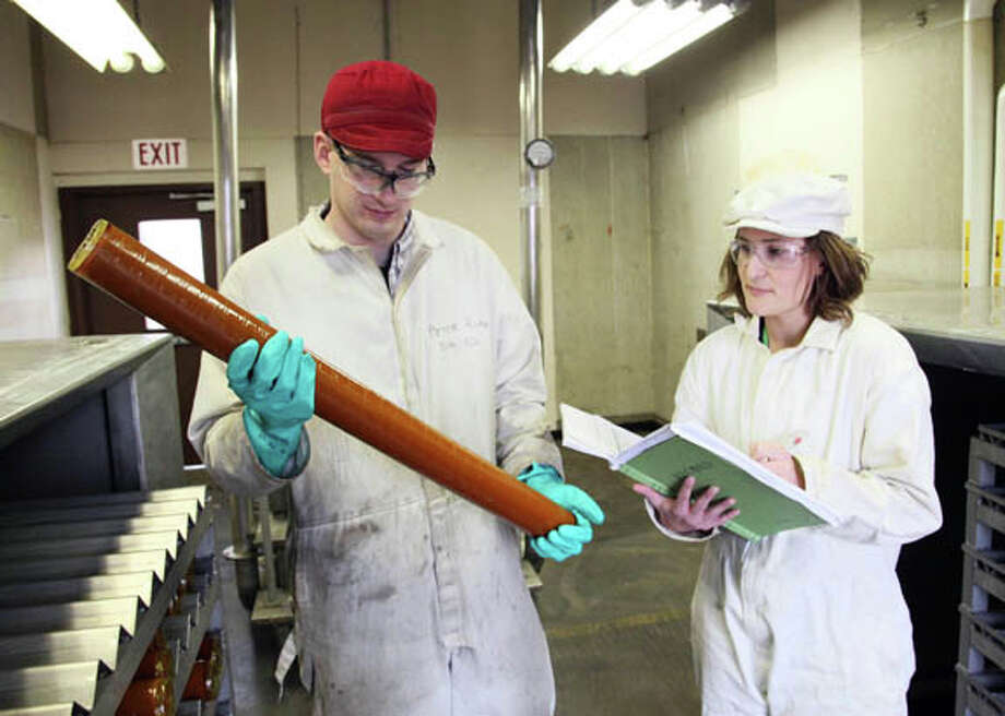 Peter Rohr, an engineer on Naval Surface Warfare Center, Indian Head Division's Mk 90 Propellant Grain Production line, helps Bernadette Wackerle inspect a wrapped propellant grain ready for the next step in the production process. Photo: Photo Provided