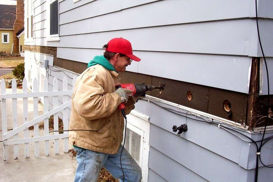 Photo submittedA RetroFoam employee drills an access hole into the side of a home so it can be filled with insulating foam.