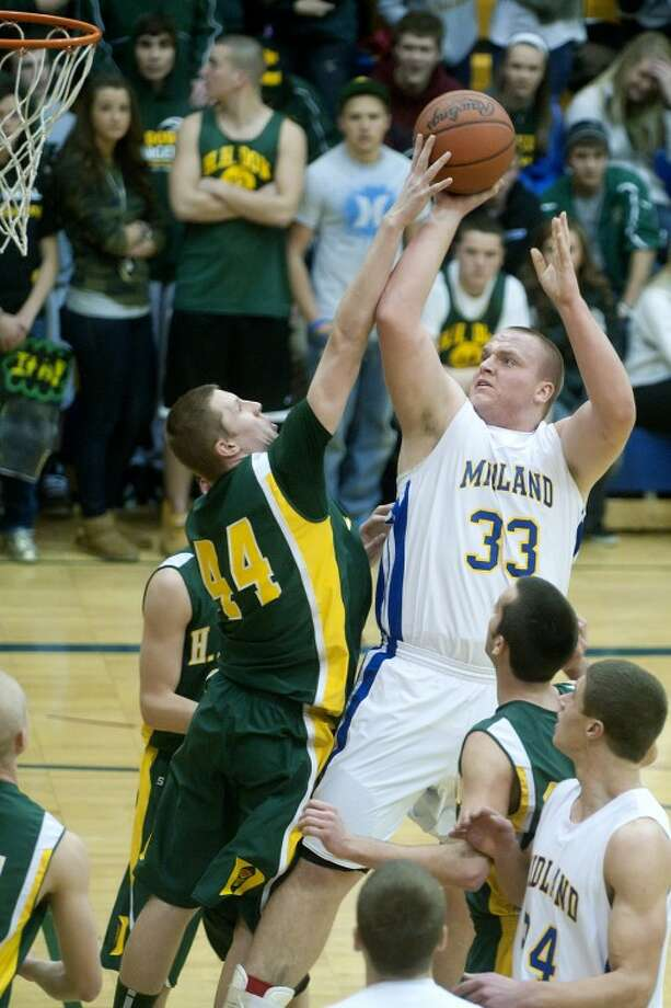 Dow's Brandon Calhoon, left, challenges at shot by Midland's Joseph Vieau during the first period Friday at Midland High School. Dow beat Midland 64-52. Photo: NICK KING | Nking@mdn.net
