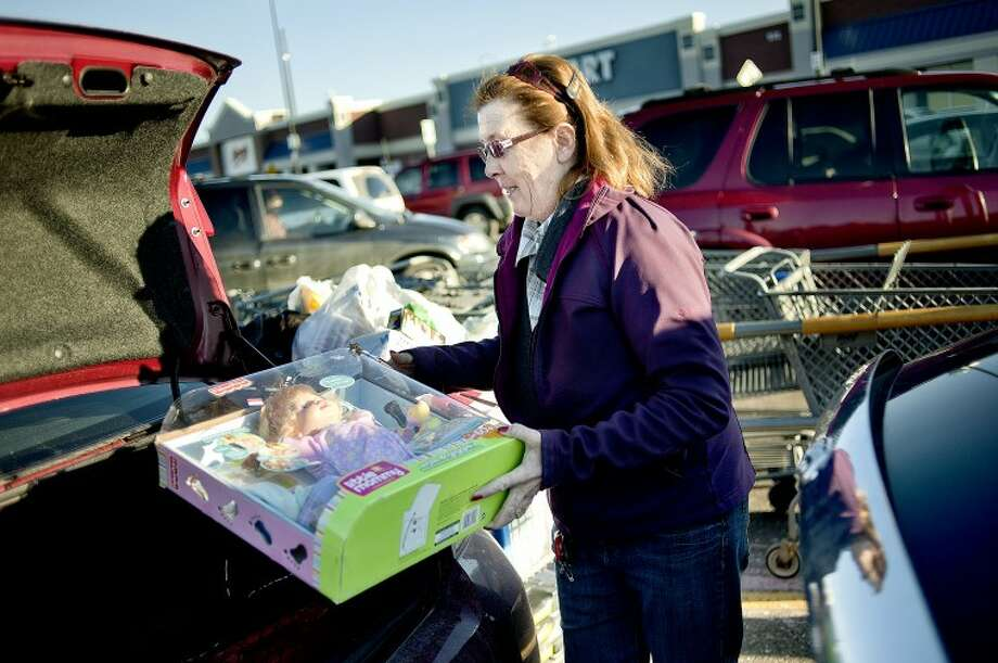 Dawn Russell loads purchases into her trunk after an after-Christmas shopping trip to Wal-Mart Monday in Midland. Russell likes shopping after the holiday because of the great deals and fewer crowds. Russell made trips to various stores after Christmas. Photo: NICK KING | Nking@mdn.net