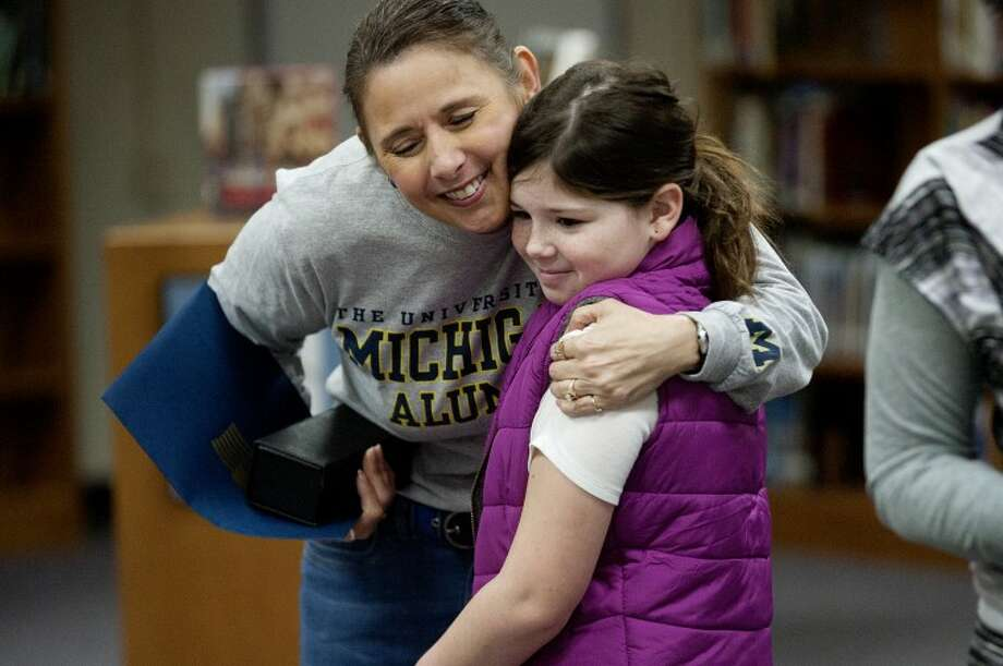 NEIL BLAKE | nblake@mdn.netCentral Middle School counselor Fran Martinez hugs Allie Clipper, 10, of Midland after Martinez received an award from the Michigan National Guard on Monday morning at the school. Photo: Neil Blake/Midland  Daily News