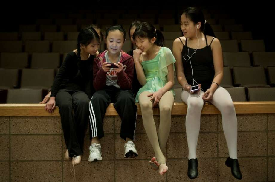NEIL BLAKE   nblake@mdn.netFrom left, Joey Meilink, 9, Julia Fu, 11, Sarah Zhao, 11, and Hannah Loveless, 11, kill time while waiting for their turn to rehearse at Bullock Creek High School for the Tri-City Chinese Association Chinese New Year Celebration. The girls practice dance each week taught by Chinese dance instructor Xiaogian Meng, a senior at Saginaw Valley State University. Photo: Neil Blake\u002fMidland  Daily News