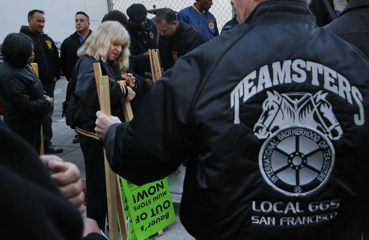 Mary Higgins passes out picket signs during a Teamsters protest against Bauer's Intelligent Transportation shuttles at a Muni stop used also for tech buses on 8th and Market streets March 22, 2016 in San Francisco, Calif.
