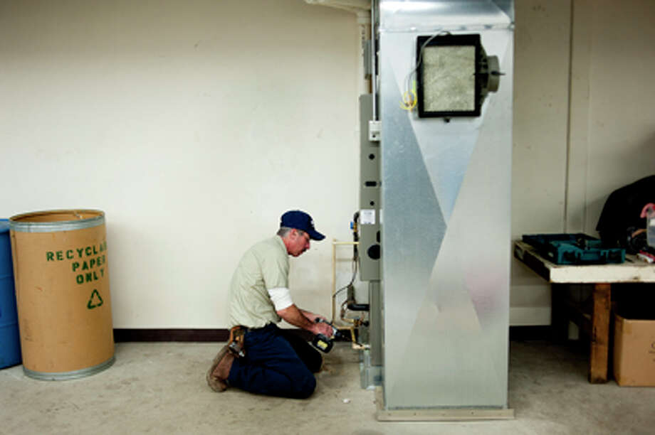 Reliable Heating and Cooling employee Pete Campau, of Sanford, installs a humidifier at Reliable Heating and Cooling in Midland for the office area. They decided to install a unit to bring up the moisture levels in the office portion of their building. Photo: NEIL BLAKE   Nblake@mdn.net  / Midland Daily News   Neil Blake