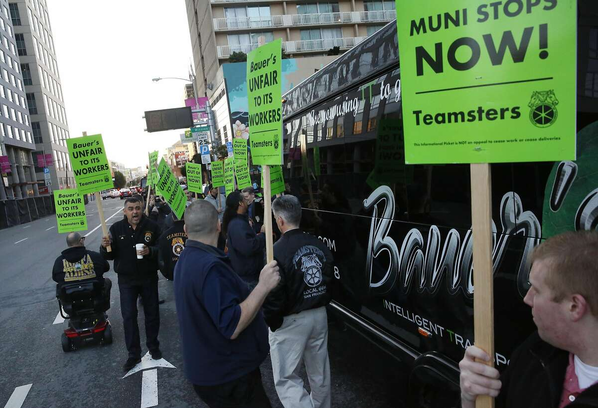 Ray Torres, left, leads chants as other Teamsters surround a Bauer's Intelligent Transportation bus during a protest against the company at a Muni stop used also for tech buses on 8th and Market streets March 22, 2016 in San Francisco, Calif.