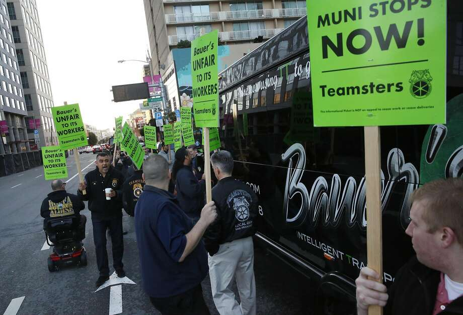 Ray Torres, left, leads chants as other Teamsters surround a Bauer's Intelligent Transportation bus during a protest against the company at a Muni stop used also for tech buses on 8th and Market streets March 22, 2016 in San Francisco, Calif. Photo: Leah Millis, The Chronicle