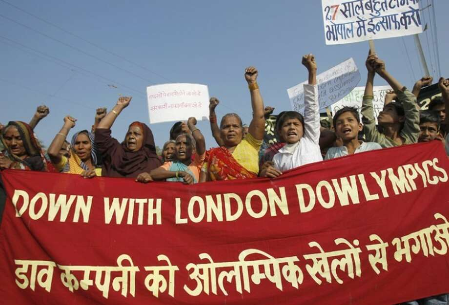 Survivors of the Bhopal gas tragedy along with other supporters shout slogans during a protest against a sponsorship deal with The Dow Chemical Co. for the 2012 Olympics in Bhopal, India, Friday. The protests came on the eve of the 27th anniversary of a lethal gas leak from a Union Carbide pesticide plant in Bhopal that killed an estimated 15,000 people died and maimed tens of thousands. Photo: Rafiq Maqbool