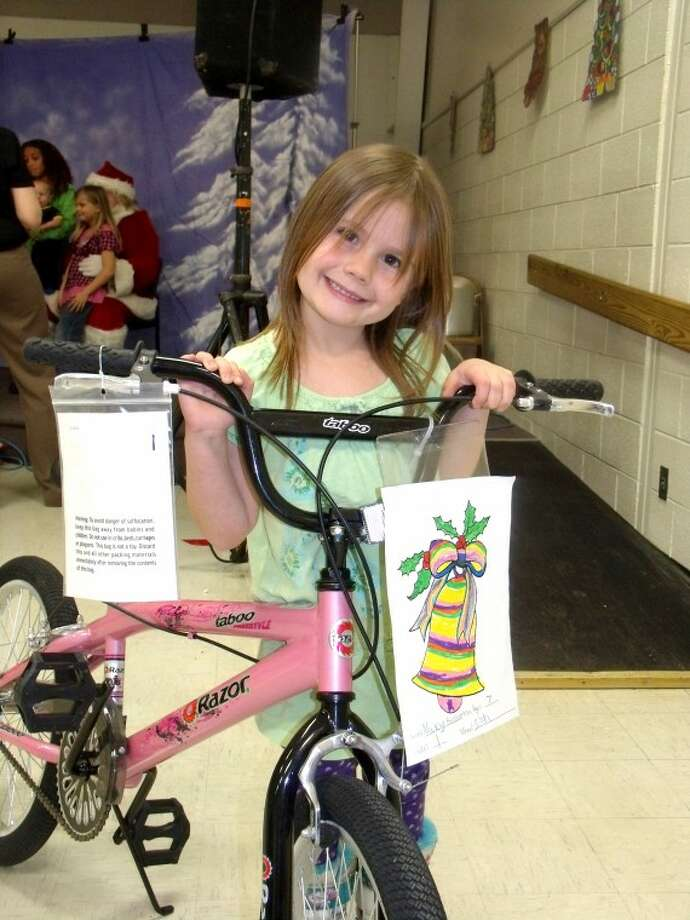 Coloring contest winner Naxy Brotherton, 7, a first grader at Zion Elementary shows off her new bike at the Auburn Santa Fun Fest on Tuesday. Photo: Submitted Photo