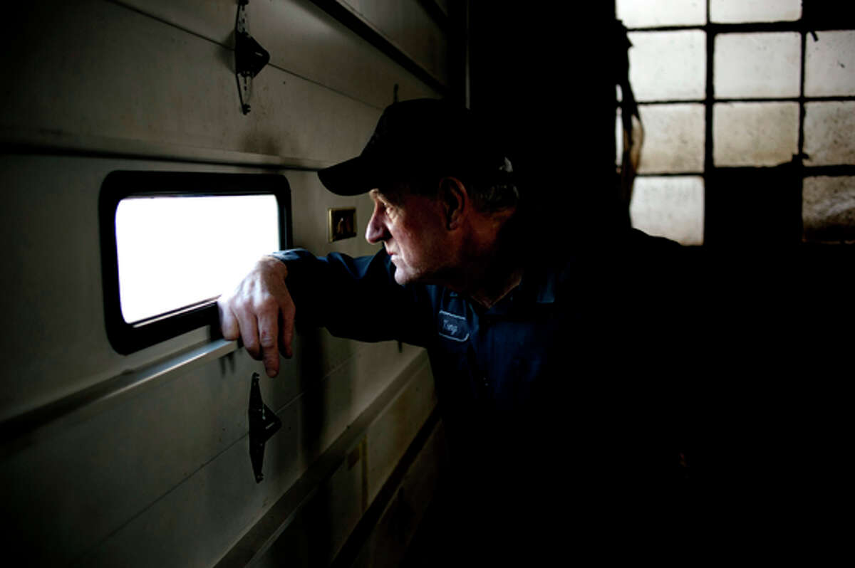 Tony Lee Myers Sr. peeks out a garage window at Henderson Brothers Rust Proofing in Midland.