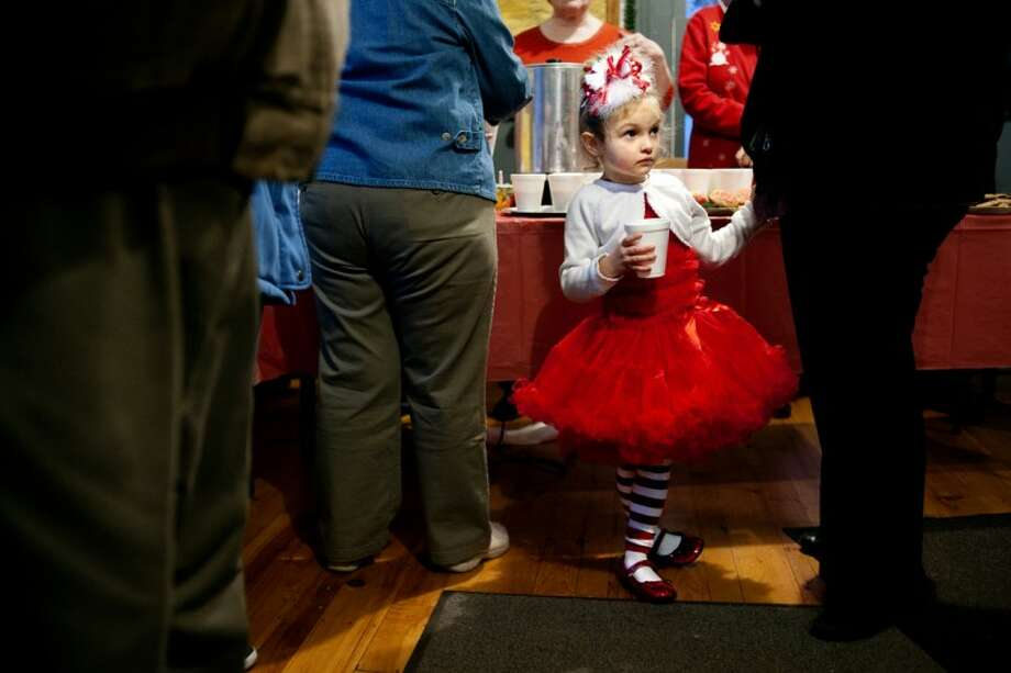 THOMASSIMONETTI | tsimonetti@mdn.net Mollie Smith, 4, of Hope hangs on to her mother's waist after getting her photo taken with Santa Claus at the Sanford Historical Museum's Santa Express on Tuesday. The event is one of the society's biggest, with about 500 children expected over the three-day event. It runs through Thursday. Photo: THOMASSIMONETTI | Tsimonetti@mdn.net