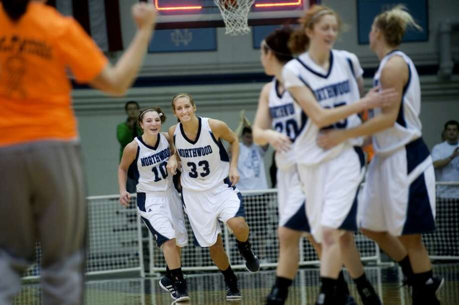 Northwood's Sarah Spring, left, and Savannah Stedman, center, celebrate the Timberwolves victory over Grand Valley State Wednesday at the Bennett Center. Photo: NICK KING | Nking@mdn.net