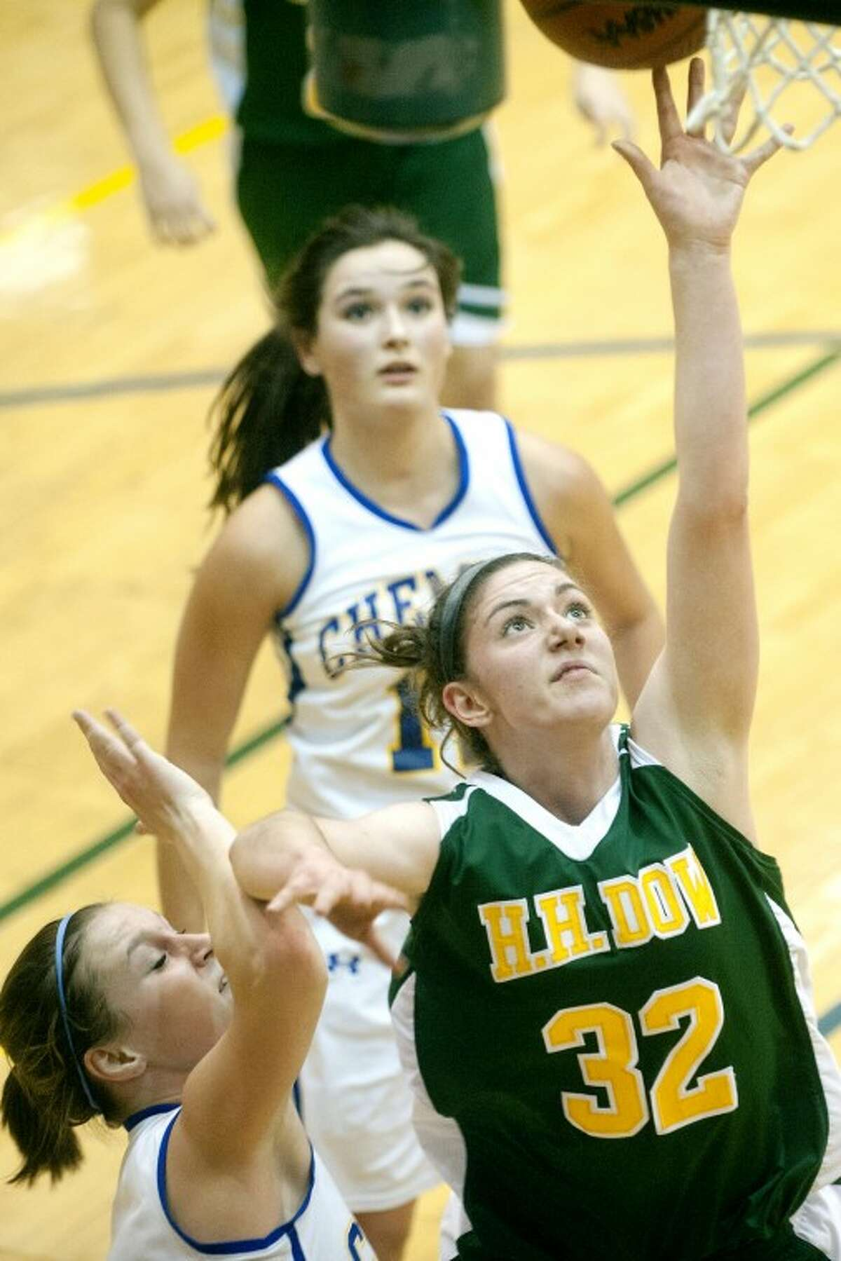 Dow's Josie Queary shoots while guarded by Midland's Jessica Walter, left, as Chemic Mikayla Russell, top, looks on in Wednesday's rivalry game at Midland.