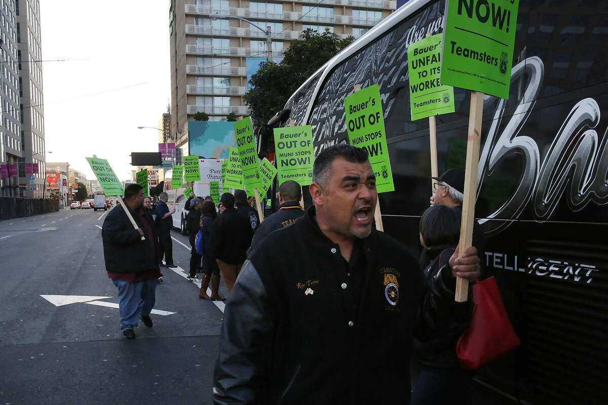 Ray Torres, right, leads chants as other Teamsters surround a Bauer's Intelligent Transportation bus during a protest against the company at a Muni stop used also for tech buses on 8th and Market streets March 22, 2016 in San Francisco, Calif.