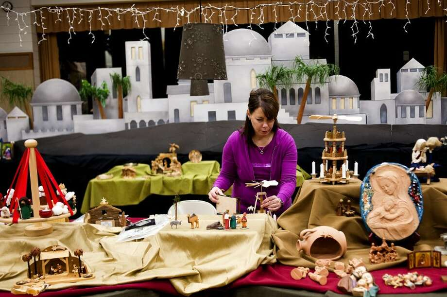 Janelle Thornton arranges nativity scenes in the international room on Thursday at the Church of Jesus Christ of Latter-Day Saints in Midland. Great care is taken in the placement of each nativity to ensure a unique viewing experience. More than 600 sets will be on display this year. Photo: NEIL BLAKE | Nblake@mdn.net