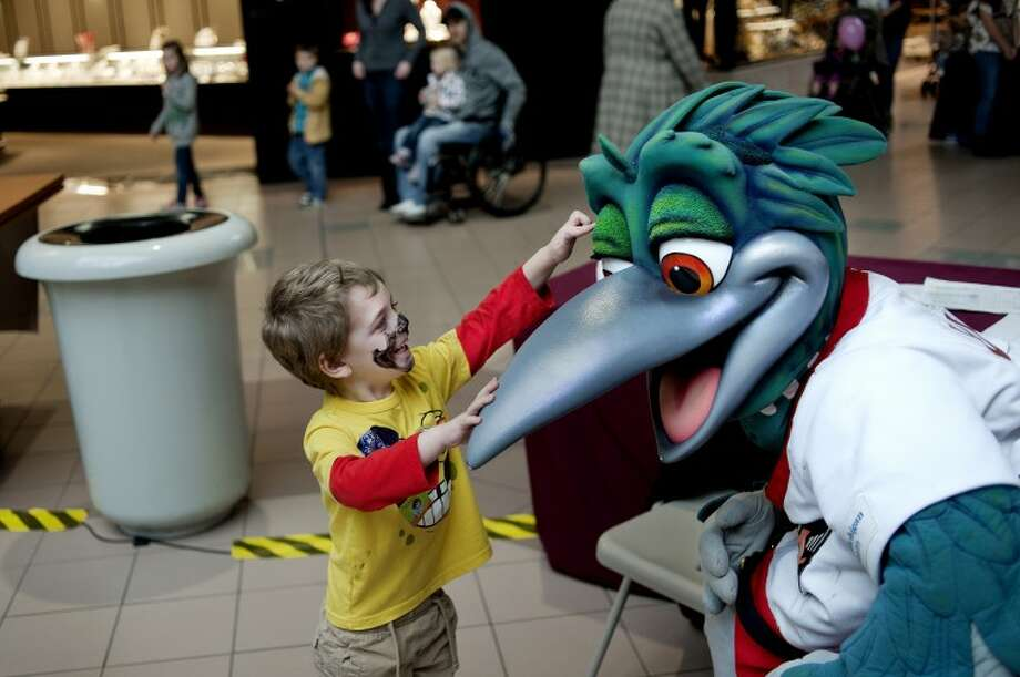 NICK KING | nking@mdn.netThree-year-old Donovan Drinkwine, left, pokes Lou E. Loon, official mascot of the Great Lakes Loons, in the eye during Kids Day 2012 Saturday at the Midland Mall. The free daylong event featured more than 50 tables from area youth-oriented organizations including the Chippewa Nature Center, Midland Gymnastics Training Center, Mid-Michigan Children's Museum and more. Performances included The White Pine Pipes & Drums and Highland Dancers, a demonstration by Yats' Tae Kwon Do, Jewls the Clown and a science presentation by Dr. Slime. Photo: Nick King/Midland  Daily News