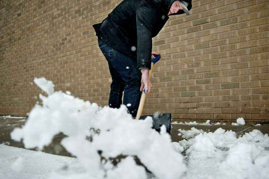 NICK KING | nking@mdn.net Matt Clement shovels snow off the sidewalk in front of Journeys coffeehouse during a snow storm that hit Midland on Tuesday. Clement, a barista at Journeys, said that the recent snow storms were evidence that winter has finally arrived. Photo: NICK KING | Nking@mdn.net