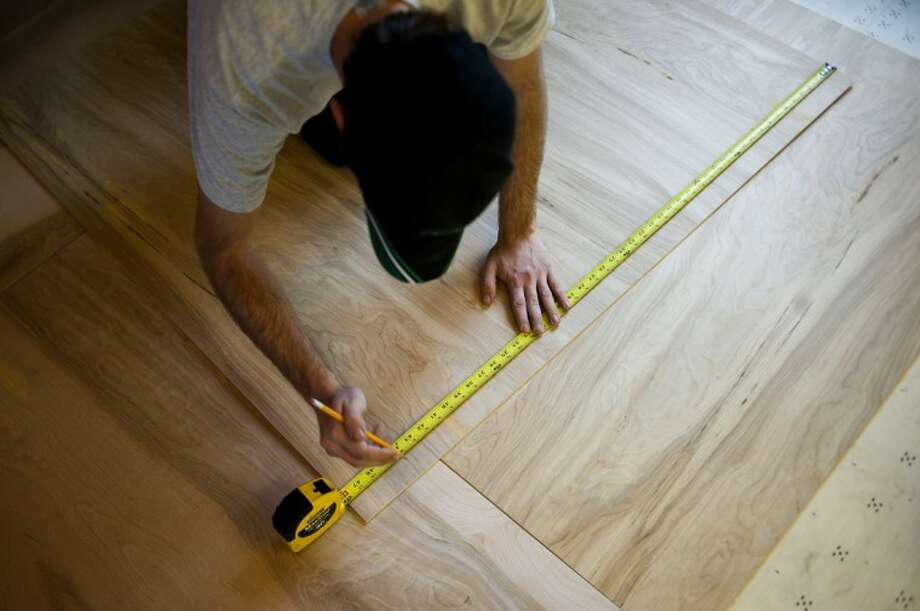 Valley Carpet, Inc. installer Tyler Bothe, of Bay City, measures a section of underlayment while working on a kitchen floor in Bay City on Wednesday. The underlayment serves as a base for the final flooring. Photo: NEIL BLAKE | Nblake@mdn.net
