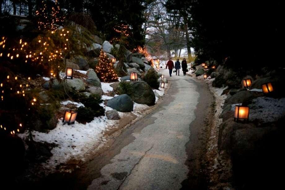 THOMAS SIMONETTI | tsimonetti@mdn.net A group walks along a lit path at Dow Gardens on Thursday at a celebration of 175 years of Michigan history. Photo: Thomas Simonetti