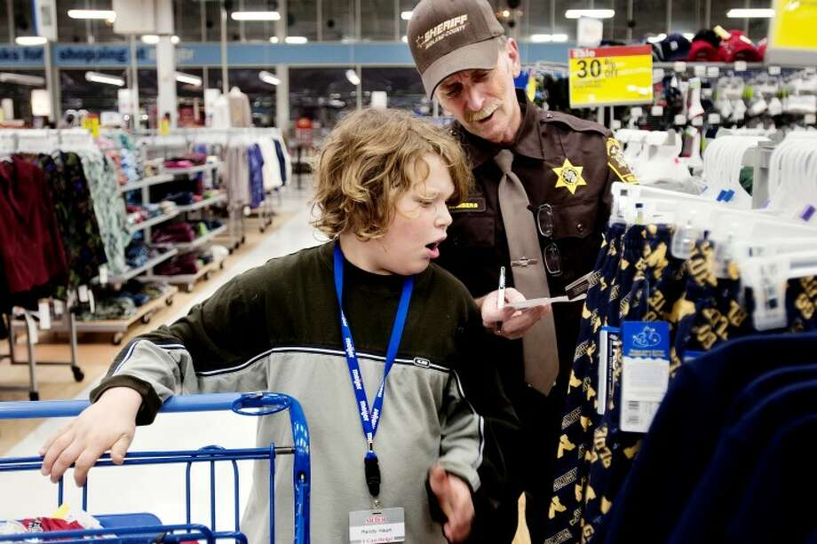 "Jim Chambers, a corrections officer with the Midland Sheriff's Department, looks at the price tag on a clothing item with Randy Hauri, 10, of Sanford, Tuesday evening during Shop With A Hero, held at Meijer on Eastman Avenue. About 25 children were chosen by the Salvation Army to go on a $100 shopping spree to, accompanied by area police, deputies, firefighters and paramedics to help them pick out gifts for family members. Hauri came with his three brothers and two cousins. ""This is a good deal great for the kids. I'm proud of the officers who come out,"" Chambers said. Photo: SEAN PROCTOR 