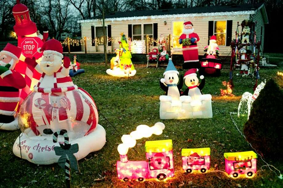 THOMAS SIMONETTI | tsimonetti@mdn.net The home of Marilyn and Tom Holsinger is decorated with dozens of Christmas inflatables. Tom Holsinger says he's been collecting the decorations, which took him about a week to set up, for about 20 years. The home is on Huntley Lane just off M-20. Photo: THOMAS SIMONETTI | Tsimonetti@mdn.net