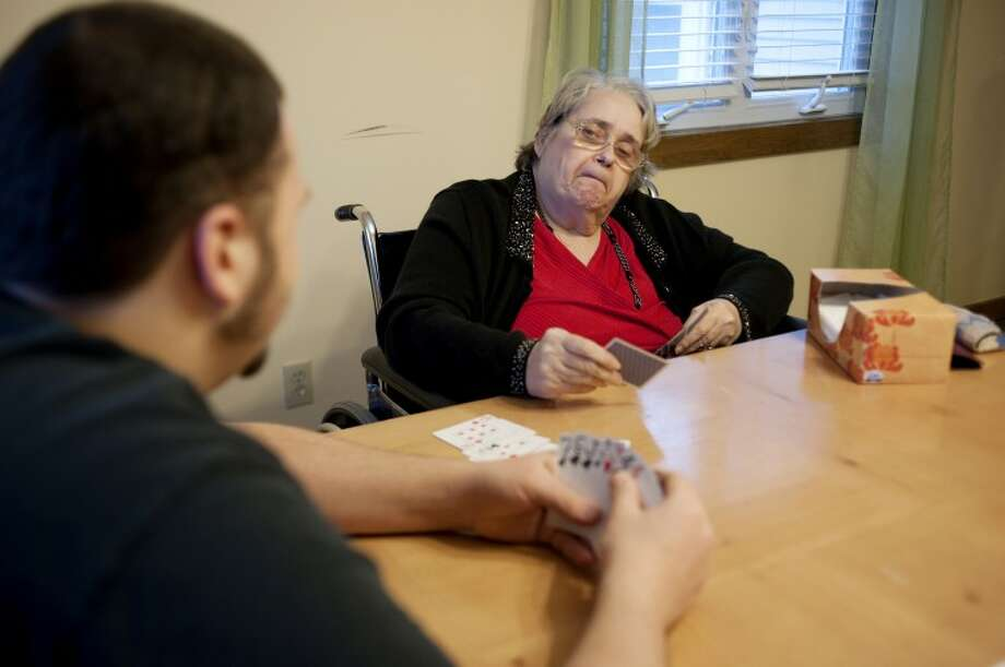 NEIL BLAKE | nblake@mdn.netKathy Pung eyes her Rummy opponent, Jordan Gray, 20, another resident at the house on Jan. 12. Kathy and Jordan usually get together to play cards every afternoon before dinner. The two are evenly matched in the game. Photo: Neil Blake/Midland  Daily News