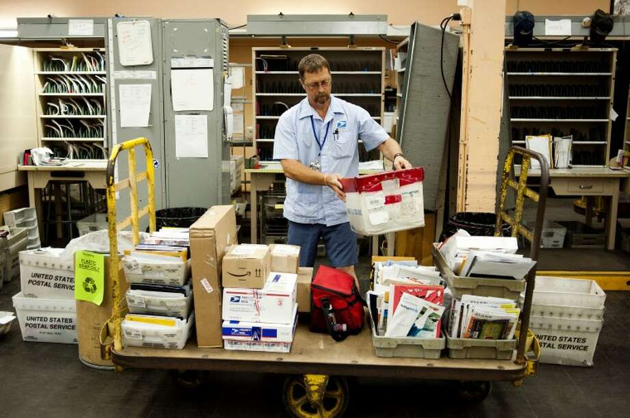 NEIL BLAKE | photo@mdn.netRick Marshall of Beaverton loads mail onto a cart at the post office on Rodd St. in Midland before going out on a route Thursday morning. Marshall, who has worked for the USPS for 22 years, has been attacked by dogs several times and was bitten two weeks ago while on a walking route. Photo: Neil Blake