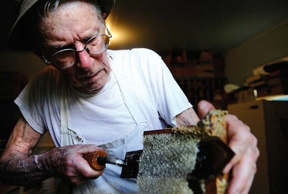Daily News/KEVIN BENEDICTJohn D. Bacon removes cappings collected on a frame with a hot knife before placing the frame in a machine to extract honey from it at his Auburn home in this file photo.