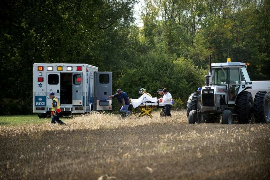 NEIL BLAKE | nblake@mdn.netThe victim in a tractor accident is taken to an ambulance off Waldo Road near the intersection of Wheeler Road on Monday.