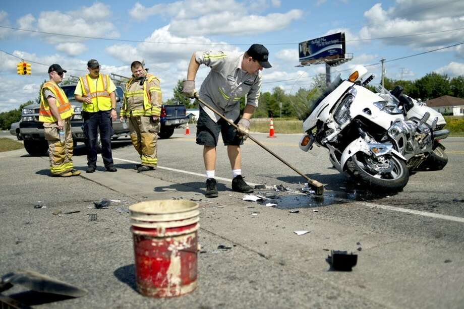 NICK KING | nking@mdn.netBrian Clifton, center, cleans up at the scene of an accident involving a truck and a motorcycle on Coleman Road near the intersection M-20 on Monday as Lee Township firefighters look on.