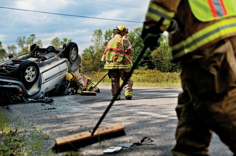SEAN PROCTOR   photo@mdn.netJerome Township firefighters clean up the road after a single-car rollover accident on West Wackerly Road between Meridian and 7 Mile Roads. Photo: Sean Proctor