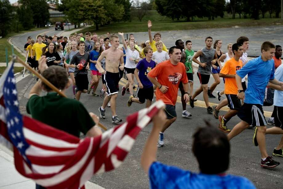 SEAN PROCTOR | photo@mdn.netSpecial Olympics athletes Jim Warner and Jenny Finzel hold an American flag and wave at runners Thursday afternoon during the Law Enforcement Torch Run for Special Olympics. Photo: Sean Proctor