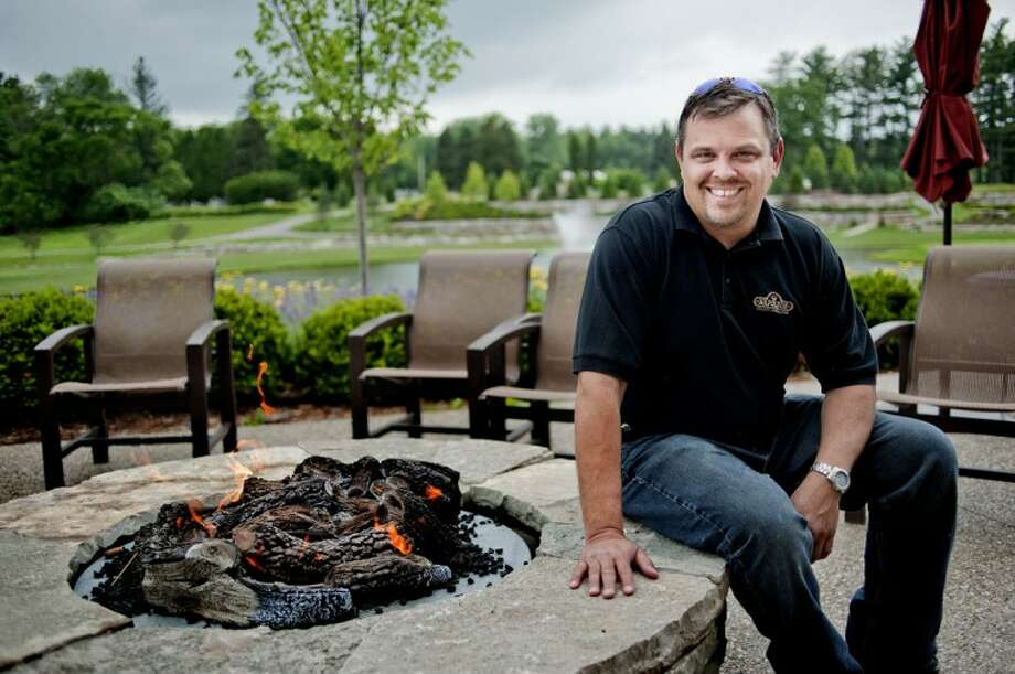 Justin Brubaker, of Brubakers' Plumbing, Heating and Air Conditioning, poses with a circular gas fire pit he installed at the Midland Country Club. Fire pits add a certain ambiance to the area in which they are installed and also give off heat. Photo: NICK KING | Nking@mdn.net