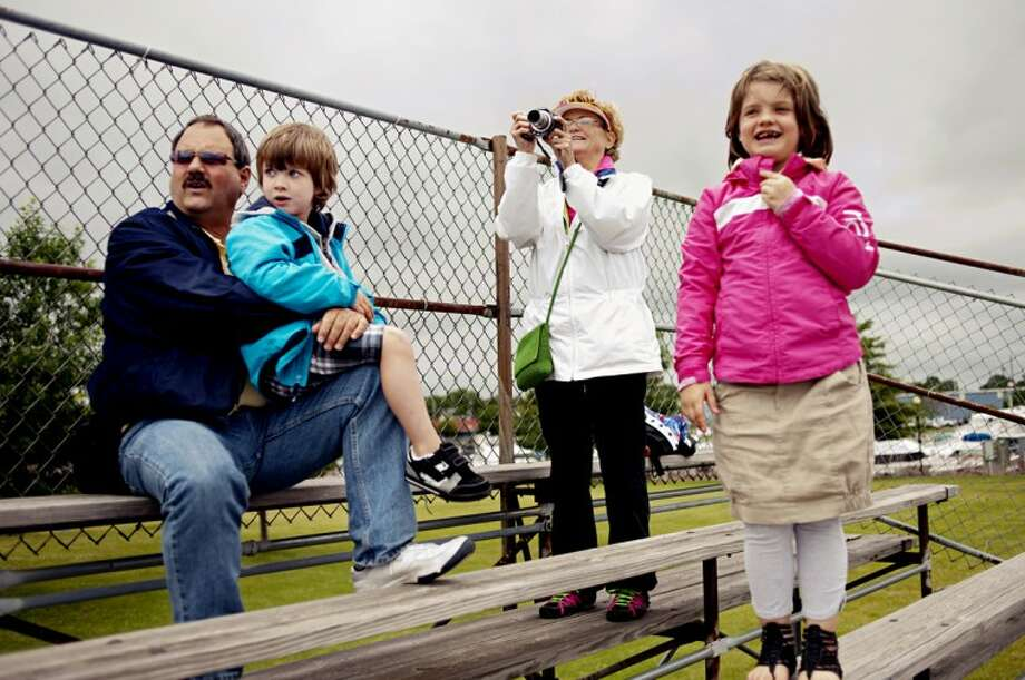 Kirk Brewster and his wife, Sherry, of Midland, watch with their grandchildren Eli Elza, 5, and Rese Elza, 7, of Sanford, as the Formula One boats take test laps on the Saginaw River on Friday at the Bay City River Roar. The Brewsters come every year to watch the warm ups but this is the first year that they've taken their grandchildren along. Photo: NEIL BLAKE | Photo@mdn.net