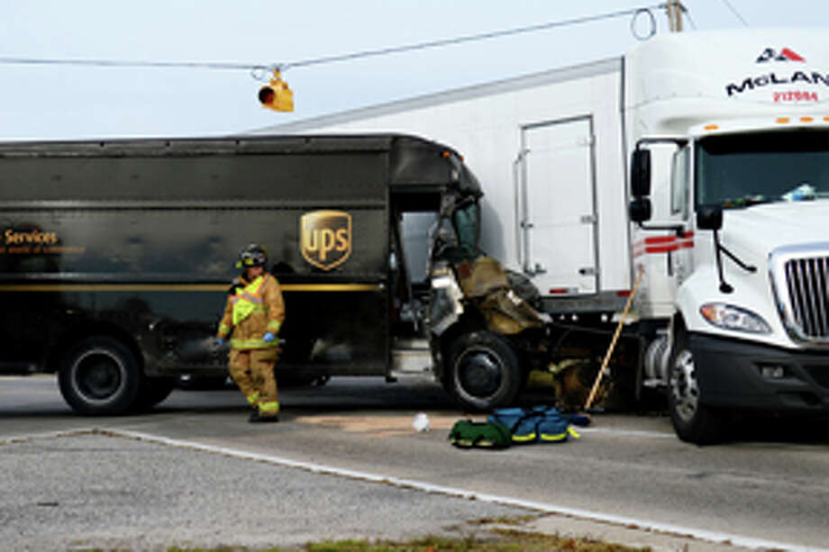 NEIL BLAKE | nblake@mdn.netMidland firefighter Justin Newman surveys the scene after a UPS worker was transported with a head injury following an accident at the crossover of Patrick Road and US-10 on Monday morning.