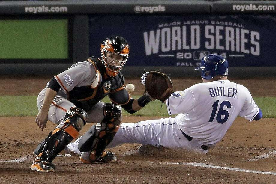 Giants Buster Posey makes a catch after Royals Billy Butler slides safely onto home plate to score in the second inning during game seven of the World Series at Kauffman Stadium in Kansas City, Missouri, on Wednesday Oct. 29, 2014. Photo: Carlos Avila Gonzalez, The Chronicle