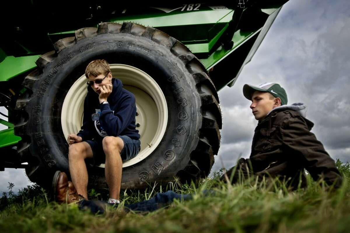 SEAN PROCTOR | photo@mdn.netSpencer Brown, 13, right, and Gavin Marr, 14, members of the Breckenridge FFA, sit and wait for the next group of students to make their way to the farm machinery station at the Laurenz family farm.