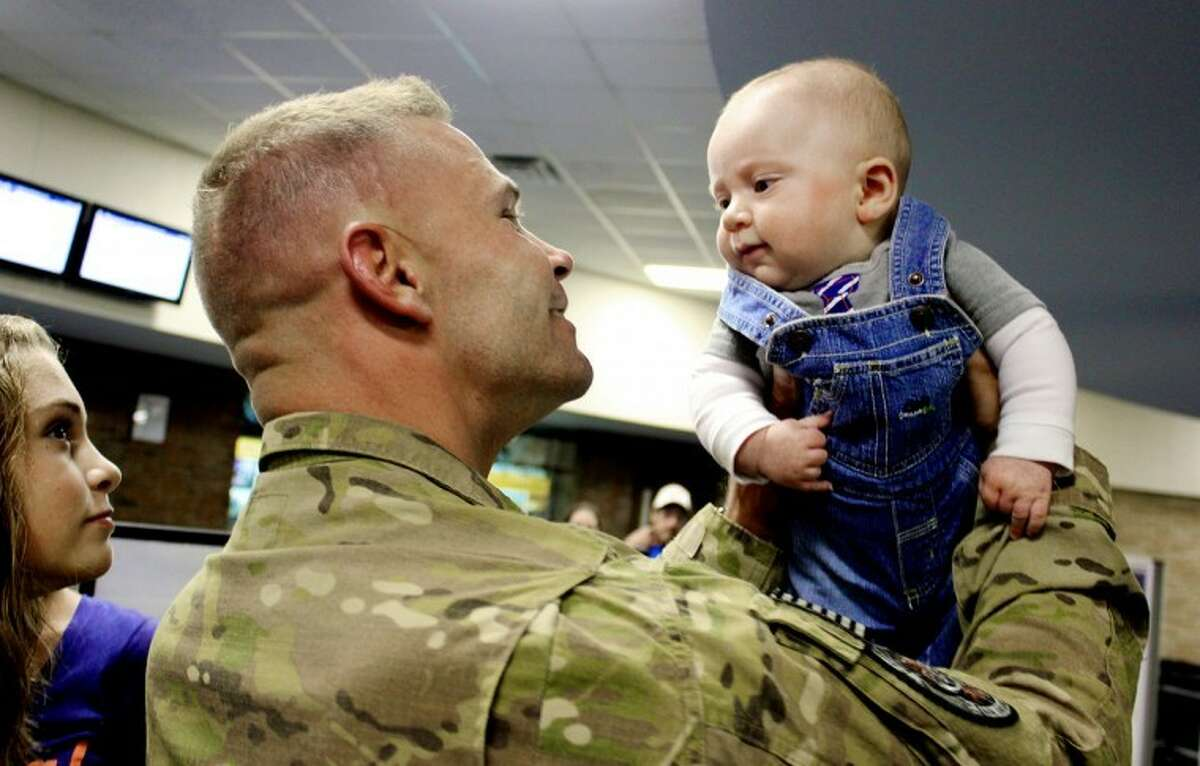 TRACY BURTON | for the Daily NewsBenjamin Gracey of the U.S. Army returns home after a one-year tour in Afghanistan and meets his 3-month-old son, Braxton, for the first time while his oldest daughter, Makenzi, looks on.