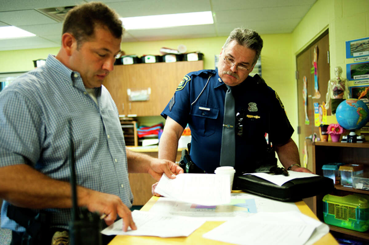 Lt. Steve Elmer of the Midland Police Department, left, and Sgt. Lance Cook of the Michigan State Police discuss the plan to set up and maintain a buffer zone around Dow Chemical, Dow Corning and MCV at the staging area at Messiah Lutheran Church in Midland during an exercise on Wednesday. The exercise involved agencies from Midland, Bay, Saginaw, Tuscola and Genessee counties.