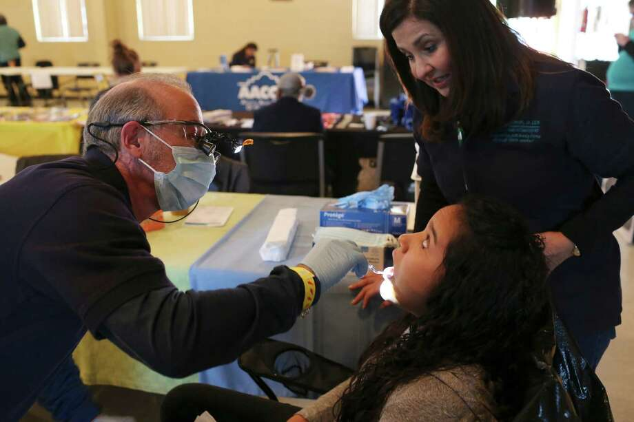 Drs. Billy and Sylvia Stewart perform a dental screening on Dalila Portillo, 17, during the Catholic Charities wellness and community resources fair at Holy Redeemer Catholic Church on Sunday, part of National Nutrition Month. Photo: Photos By Jerry Lara / San Antonio Express-News / © 2016 San Antonio Express-News