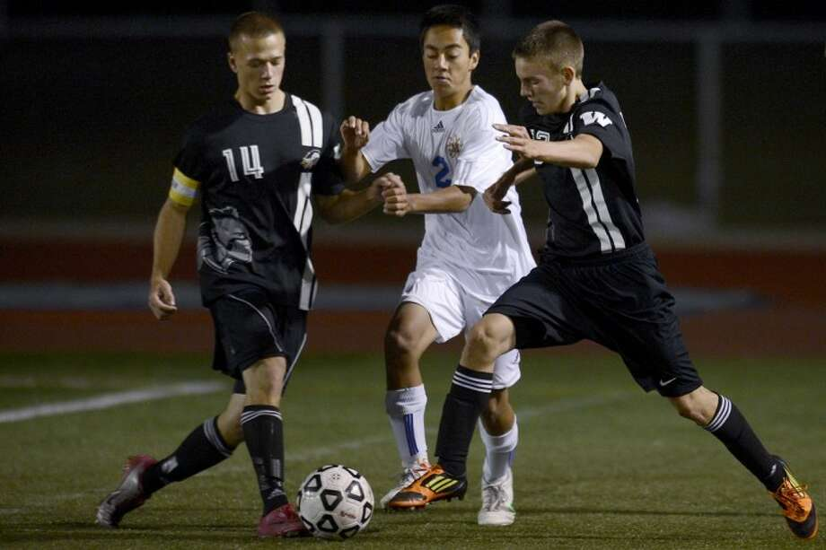 NICK KING | nking@mdn.netMidland's Justin Johnson, center, goes for the ball between Bay City Western's Briton Ott, left, and Duncan Holman Monday at Midland Stadium. Midland won 3-1. Photo: Nick King/Midland  Daily News