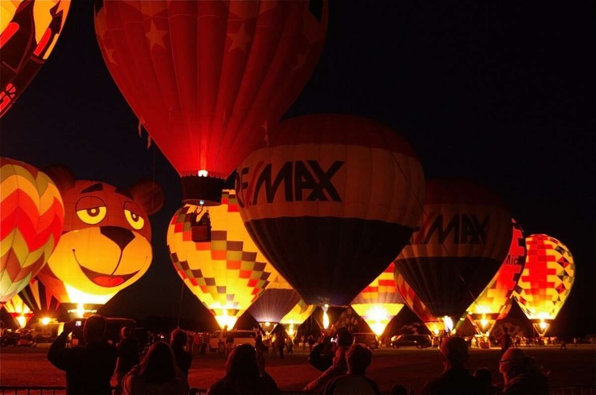 STUART FROHM for the Daily NewsSpectators watch and photograph glowing tethered balloons Saturday at the Midland County Fairgrounds during the RE/MAX Balloon Festival.