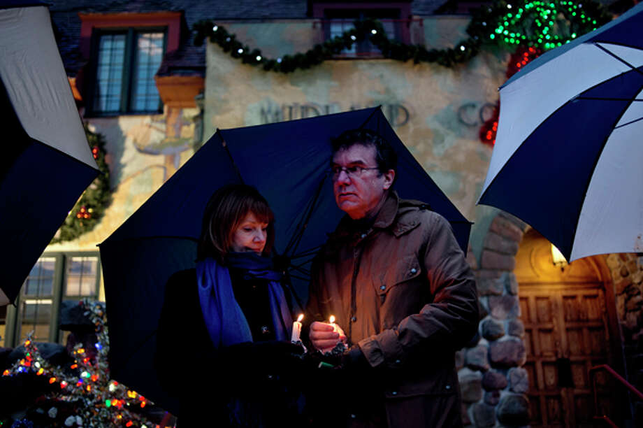 Rick and Catherine Lundgard, of Midland, huddle under their umbrella and shield their candles from the wind Saturday evening outside of the Midland County Courthouse during a candlelight vigil for the victims of the Sandy Hook Elementary School shooting that occurred on Friday in Connecticut. The vigil was organized by Char Taber, who works with Catherine at the Grace A. Dow Memorial Library. Photo: Sean Proctor / (c) Sean Proctor (c) Midland Daily News