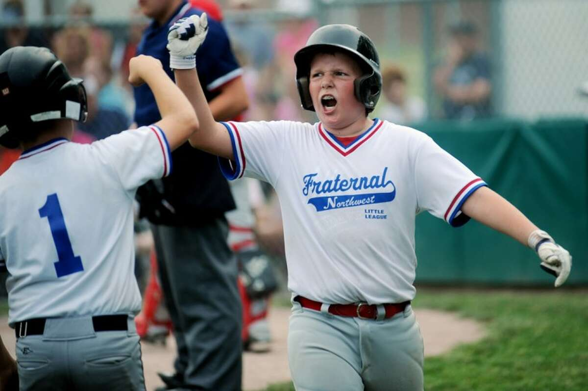 Voiture's Derek Cushman, right, celebrates a run with teammate Trevor Davis during the Little League City Championship game against Voiture at Deitz Memorial Field in Midland on Tuesday. Voiture of the Fraternal Northwest Little League defeated Kiwanis of the Fraternal Northwest Little League 4-3.