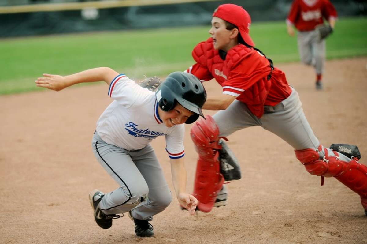 Kiwanis catcher Michael Lambesis tags out Voiture baserunner Trevor Davis between second and third during the Little League City Championship at Deitz Memorial Field in Midland on Tuesday. Voiture of the Fraternal Northwest Little League defeated Kiwanis of the Fraternal Northwest Little League 4-3.
