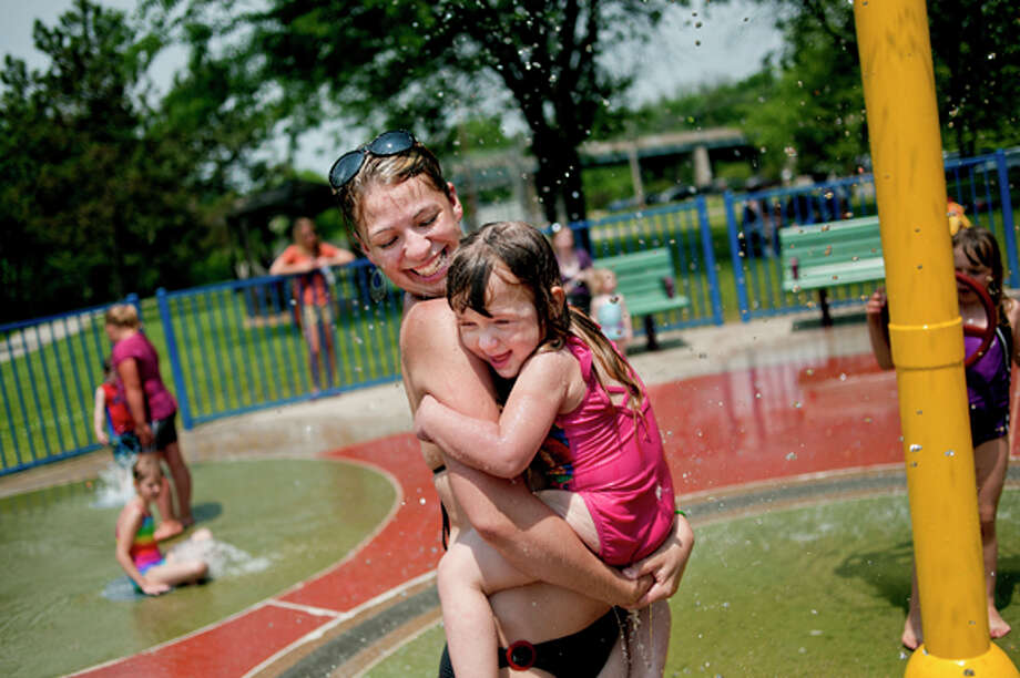 Jennifer Vogel, left, carries her 3-year-old daughter Adalyn through a fountain at the Gerstacker Sprayground at Chippewassee Park. Vogel, of Freeland, brought her daughter to the park to cool off after hearing that another hot day was on tap for Midland. (File photo)