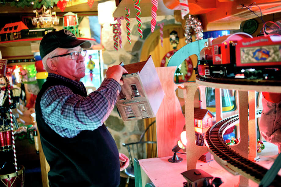 Tom Valent arranges a building donated by the Church family into his toy train display recently at the Santa House. Valent says that over time he will be incorporating more parts of the Church train collection into the Santa House for Midlanders to enjoy. Photo: Nick King/Midland  Daily News / Midland Daily News