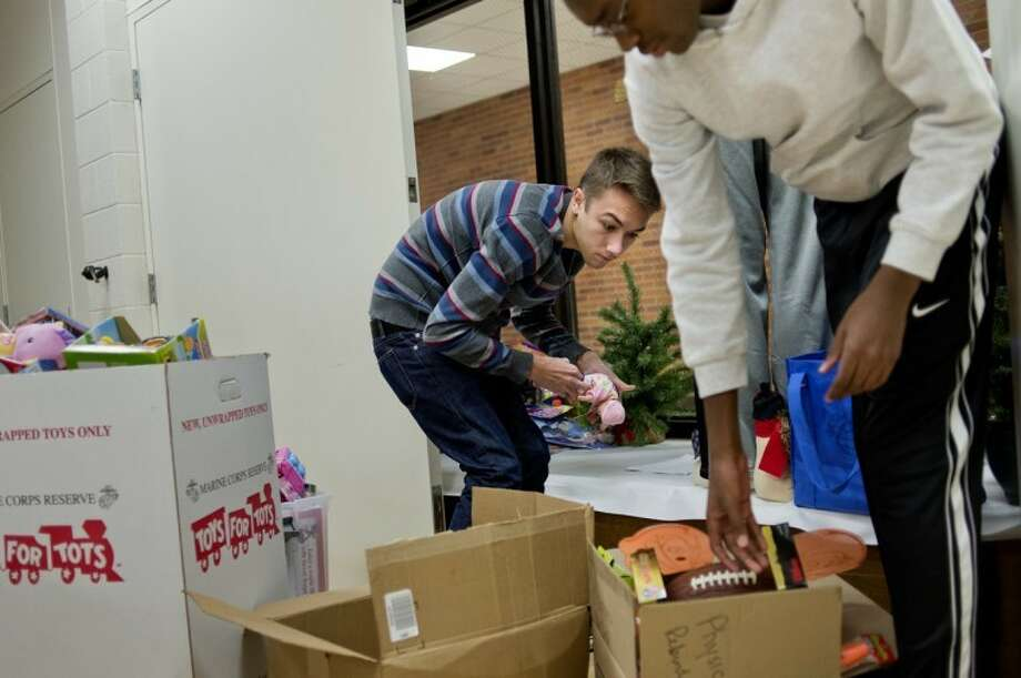 NICK KING | nking@mdn.netDow High students Kris Anderson, 17, left, and Kofi Ofori-Darko, 14, remove toys from a display window and pack them up at the end of the DECA Club-sponsored Toys for Tots drive. Photo: Nick King/Midland  Daily News