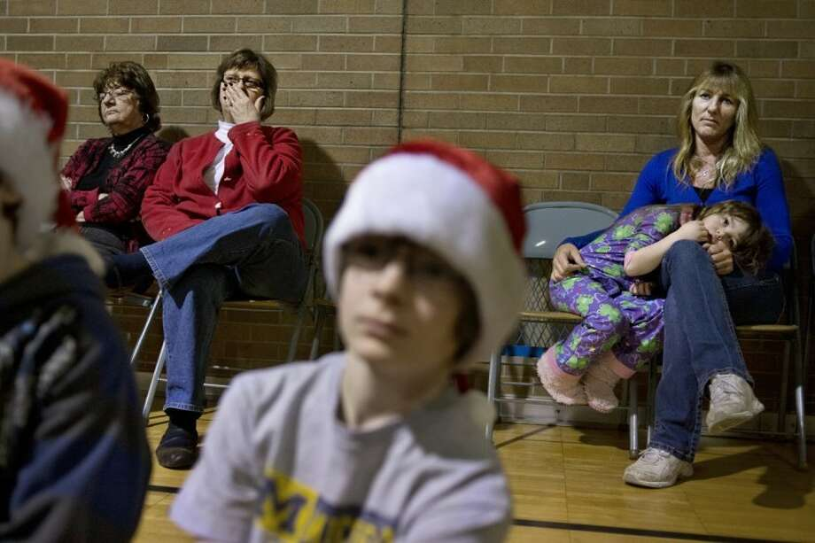 SEAN PROCTOR | sproctor@mdn.netEllen Burrell, a paraprofessional at Chestnut Hill Elementary School, sits with Moira Finney, 5, and listens as Cheryl Levy, dressed as Mrs. Claus, tells stories and sings songs Friday morning at the school. After the assembly, students returned to their classroom to enjoy their Christmas parties. Photo: Sean Proctor